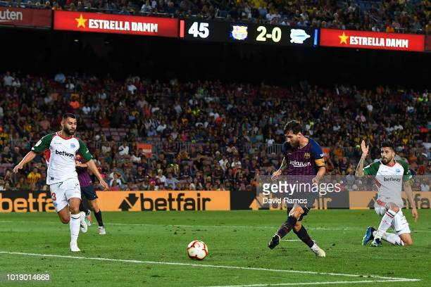 Lionel Messi of FC Barcelona scores his team's third goal during the La Liga match between FC Barcelona and Deportivo Alaves at Camp Nou on August 18...