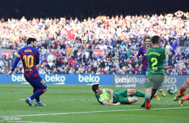 Lionel Messi of FC Barcelona scores his team's third goal during the La Liga match between FC Barcelona and SD Eibar SAD at Camp Nou on February 22...