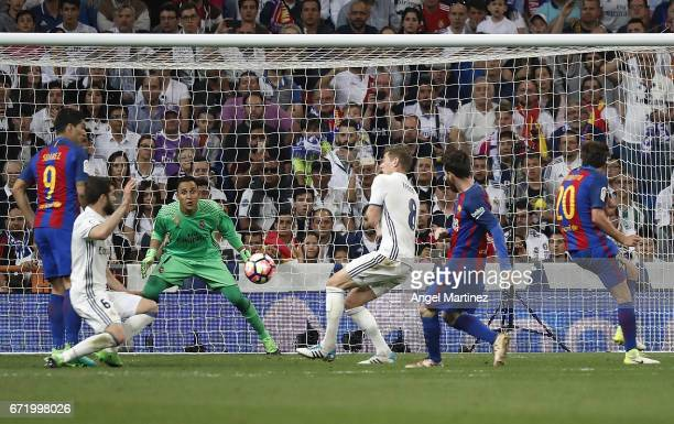 Lionel Messi of FC Barcelona scores his team's third goal during the La Liga match between Real Madrid and FC Barcelona at Estadio Santiago Bernabeu...