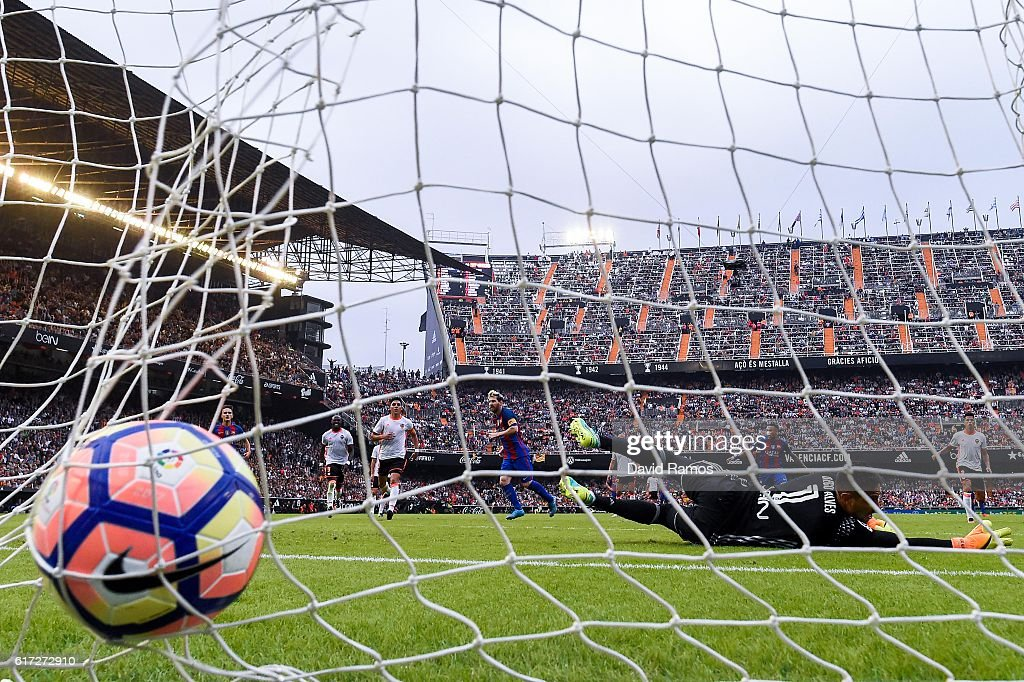 Lionel Messi of FC Barcelona scores his team's third goal from the penalty spot during the La Liga match between Valencia CF and FC Barcelona at Mestalla stadium on October 22, 2016 in Valencia, Spain.
