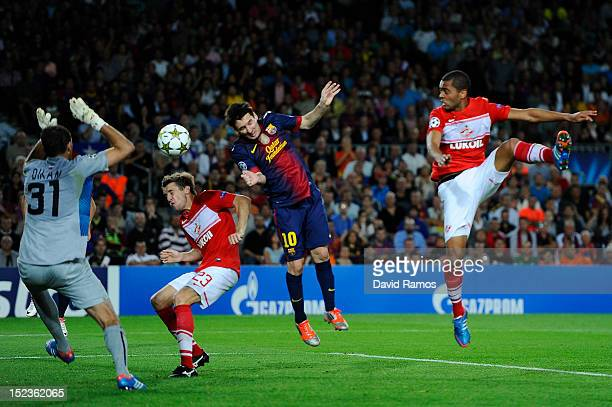 Lionel Messi of FC Barcelona scores his team's third goal past Dmitry Kombarov of FC Spartak Moscow during the UEFA Champions League Group G match...