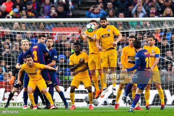 Lionel Messi of FC Barcelona scores the opening goal during the La Liga match between Barcelona and Atletico Madrid at Camp Nou on March 4 2018 in...