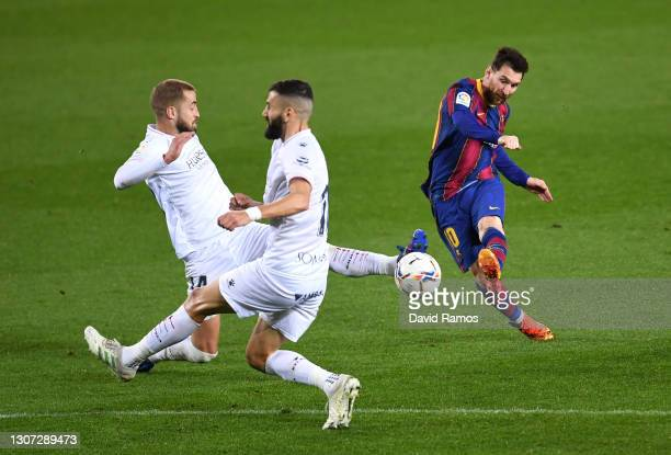 Lionel Messi of FC Barcelona scores their side's fourth goal during the La Liga Santander match between FC Barcelona and SD Huesca at Camp Nou on...
