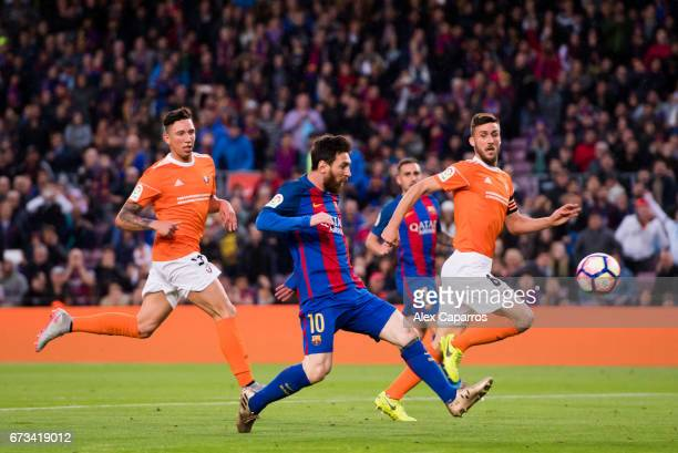 Lionel Messi of FC Barcelona shoots the ball and scores the opening goal during the La Liga match between FC Barcelona and CA Osasuna at Camp Nou...