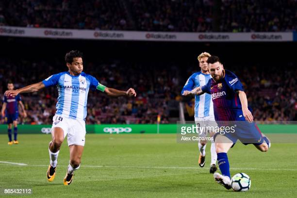 Lionel Messi of FC Barcelona shoots the ball with opposition from Roberto Rosales of Malaga CF during the La Liga match between Barcelona and Malaga...