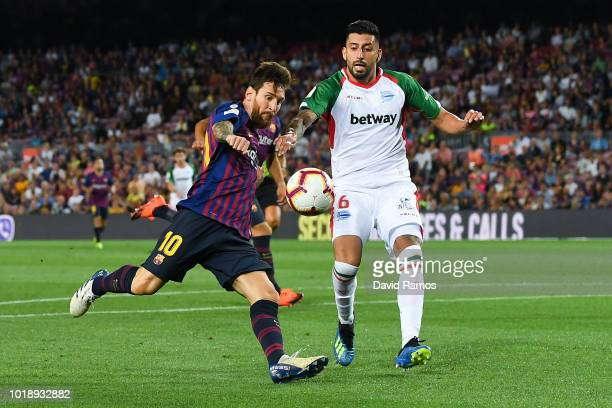 Lionel Messi of FC Barcelona shoots towards goal under a challenge by Guillermo Maripan of Deportivo Alaves during the La Liga match between FC...
