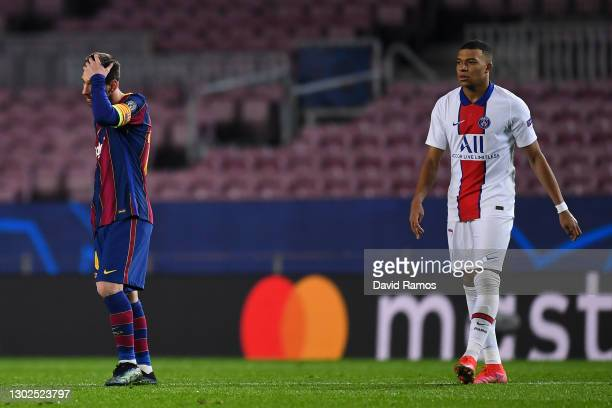 Lionel Messi of FC Barcelona shows his dejection next to Kylian Mbappe of Paris Saint-Germain during the UEFA Champions League Round of 16 match...