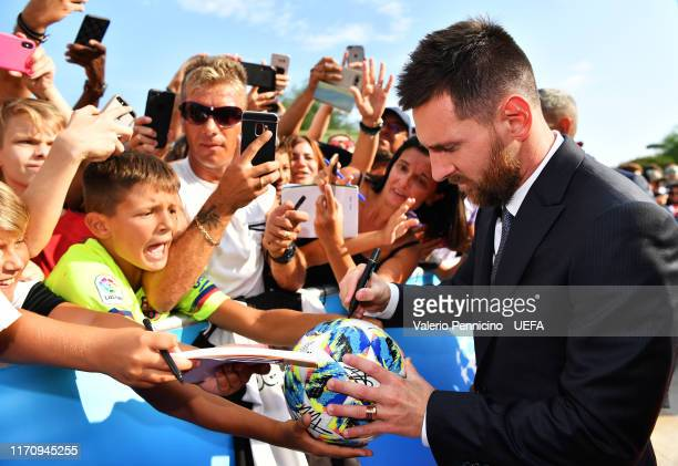 Lionel Messi of FC Barcelona signs autographs for fans as he arrives on the red carpet prior to the UEFA Champions League Draw, part of the UEFA...