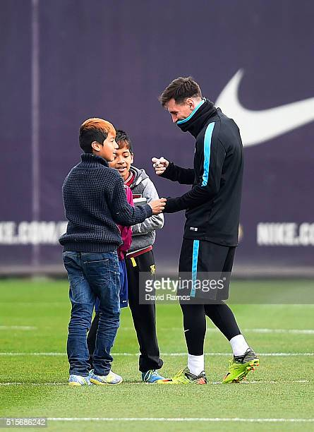Lionel Messi of FC Barcelona signs his autograph for youkng fans who ran onto the training pitch during a Barcelona training session ahead of the...