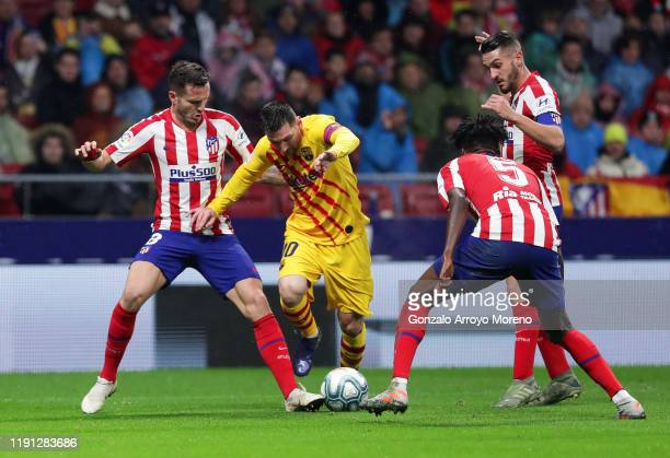 Lionel Messi of FC Barcelona takes on Saul Niguez Thomas Partey and Koke of Atletico Madrid during the Liga match between Club Atletico de Madrid and...