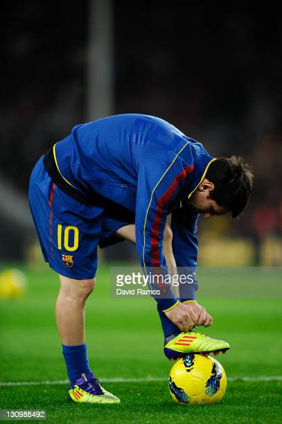 Lionel Messi of FC Barcelona ties up his boots during the warm up prior to the La Lliga match between FC Barcelona and RCD mallorca at Camp Nou on...