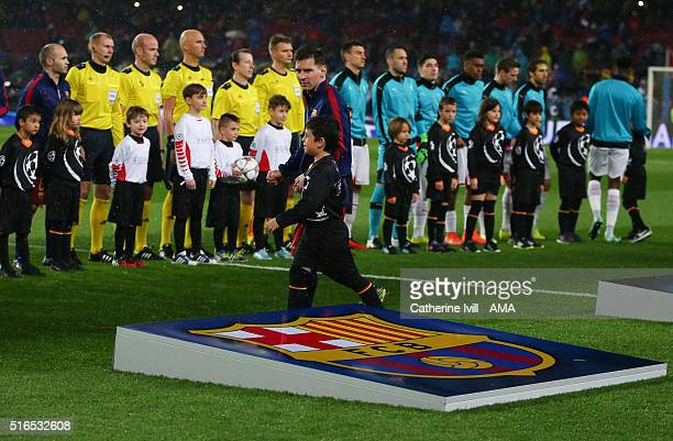 Lionel Messi of FC Barcelona walks past a giant club crest as the teams come out before the UEFA Champions League match between FC Barcelona and...
