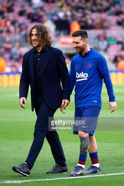 Lionel Messi of FC Barcelona walks with former teammate Carles Puyol before the La Liga match between FC Barcelona and Deportivo Alaves at Camp Nou...