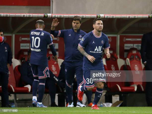 Lionel Messi of PSG is replacing Neymar Jr, left with coach of PSG Mauricio Pochettino during the Ligue 1 Uber Eats match between Stade Reims and...