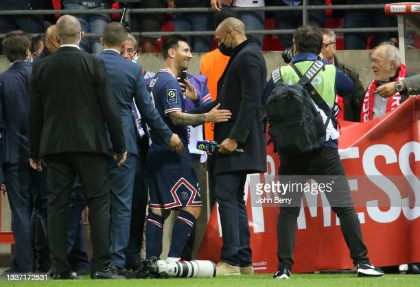 Lionel Messi of PSG salutes Thierry Henry, pundit for Amazon Prime VIdeo following the Ligue 1 Uber Eats match between Stade Reims and Paris Saint...
