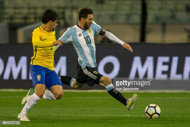 Lionel Messi of the Argentinan National Football Team controls the ball in front of Fagner Lemos of the Brazilian National Football Team during the...