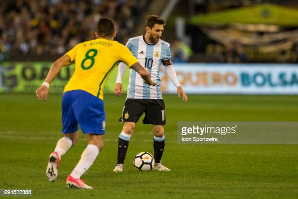 Lionel Messi of the Argentinan National Football Team controls the ball in front of Renato Augusto of the Brazilian National Football Team during the...