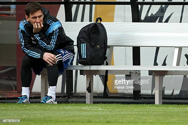 Lionel Messi of the Argentinian national soccer team sits on the bench as his teammates practice on the field in preparation to take on El Salvador...