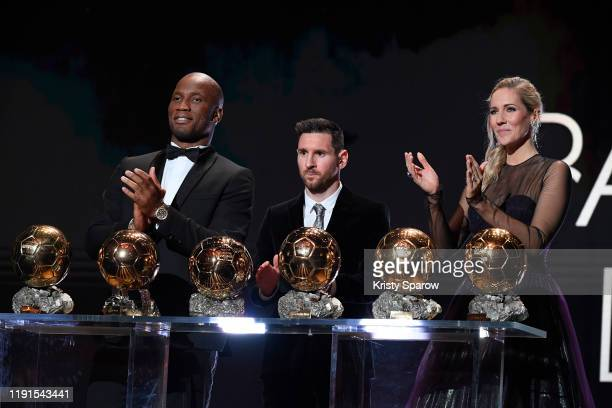 Lionel Messi poses onstage with hosts Didier Drogba and Sandy Heribert after winning his sixth Ballon D'Or award during the Ballon D'Or Ceremony at...