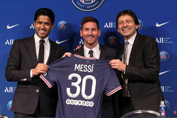 Lionel Messi poses with his jersey next to President Nasser Al Khelaifi and Leonardo after the press conference of Paris Saint-Germain at Parc des...