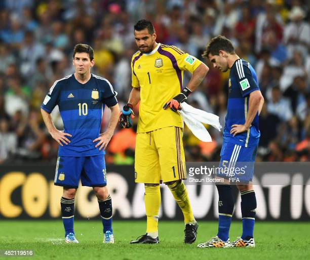 Lionel Messi Sergio Romero and Fernando Gago of Argentina show their dejection after the 2014 FIFA World Cup Brazil Final match between Germany and...