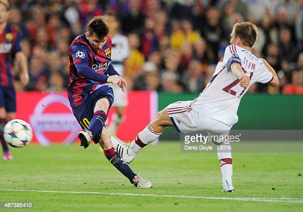 Lionel Messi shoots to score the first goal as he is challenged by Philipp Lahm of Bayern Munich during the UEFA Champions League semifinal match...