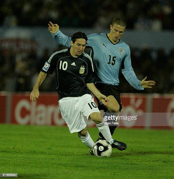 Lionel Messi vies for the ball with Diego Perez of Uruguay during their FIFA World Cup South Africa2010 qualifier football match at the Centenario...