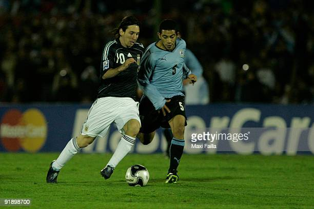 Lionel Messi vies for the ball with Walter Gargano of Uruguay during their FIFA World Cup South Africa2010 qualifier football match at the Centenario...