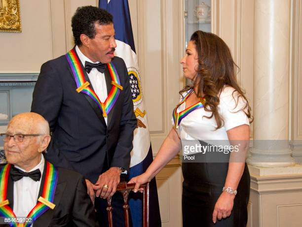 Lionel Richie and Gloria Estefan two of the five recipients of the 40th Annual Kennedy Center Honors converse after posing for a group photo...