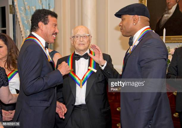 Lionel Richie left Norman Lear center and LL Cool J right three of the five recipients of the 40th Annual Kennedy Center Honors converse prior to...