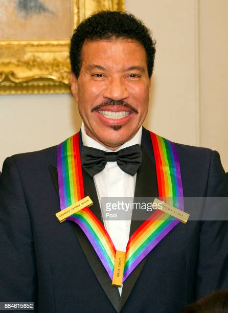 Lionel Richie, one of he five recipients of the 40th Annual Kennedy Center Honors with his award as he poses for a group photo following a dinner...