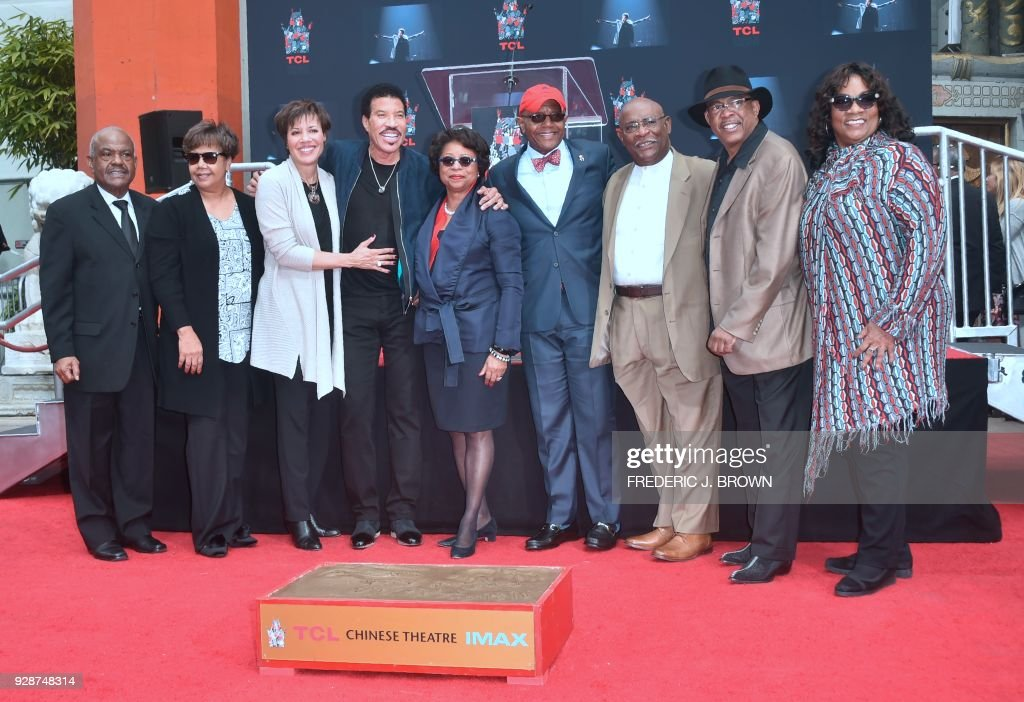 Lionel Ritchie poses with friends from his youth going back to pre-school during his Hand and Footprints ceremony at the TCL Theater on March 7,2018 in Hollywood, California. /