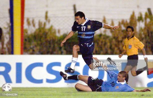 Lionel Scaloni of Argentina jumped over Javier Chevanton of Uruguay 04 February 2000 in Londrina Brazil Both teams fought for a place in the Summer...
