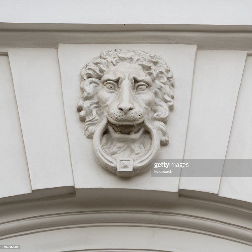 Lions face statue carved on the wall of a building : Stock Photo