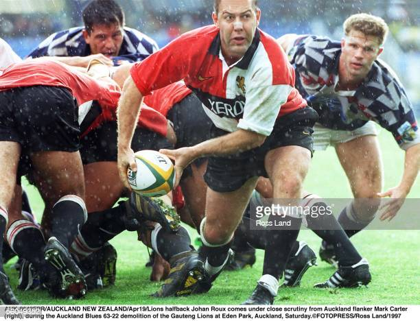 Lions halfback Johan Roux comes under close scrutiny from Auckland flanker Mark Carter r during the Auckland Blues 6322 demolition of the Gauteng...