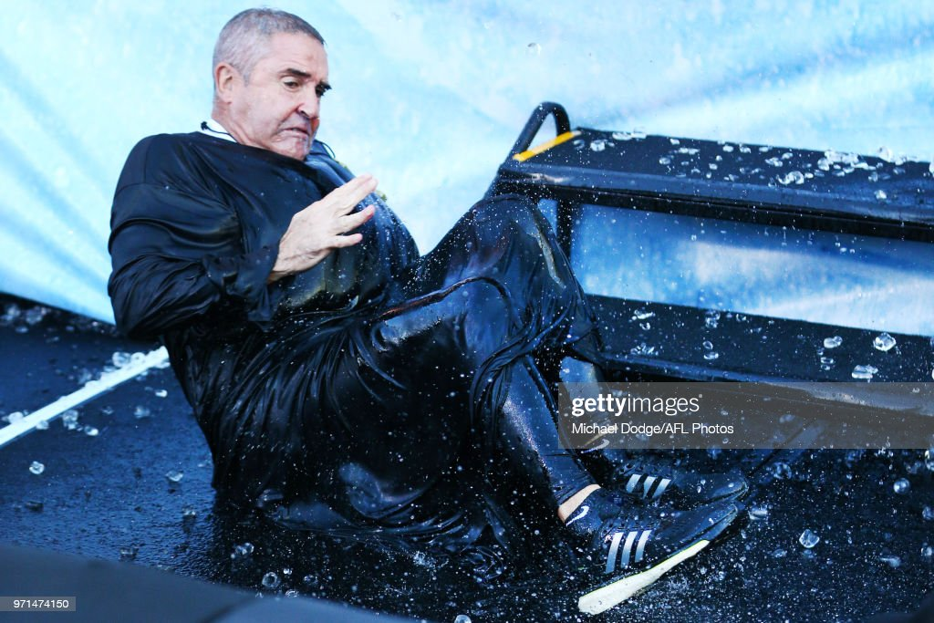 Lions head coach Chris Fagan falls after sliding down the MND slide during the round 12 AFL match between the Melbourne Demons and the Collingwood Magpies at Melbourne Cricket Ground on June 11, 2018 in Melbourne, Australia.
