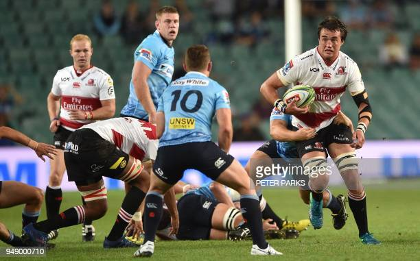 Lions player Franco Mostert runs with the ball towards Waratahs' Bernard Foley during the Super Rugby match between Australia's New South Wales...