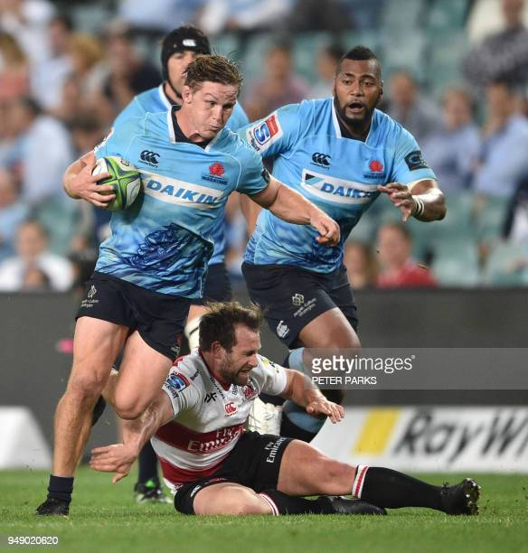 Lions player Nic Groom misses a tackle on Waratahs player Michael Hooper as teammate Sekope Kepu looks on during the Super Rugby match between...