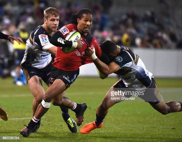 Lions player Sylvian Mahuza is tackled by Brumbies player Wharenui Hawera and Brumbies player Kyle Godwin during the Super Rugby match between the...