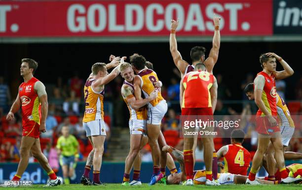 Lions players celebrate their win during the round one AFL match between the Gold Coast Suns and the Brisbane Lions at Metricon Stadium on March 25...