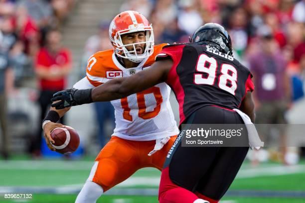 Lions quarterback Jonathon Jennings prepares himself to be saked by Ottawa RedBlacks defensive lineman Avery Ellis during Canadian Football League...