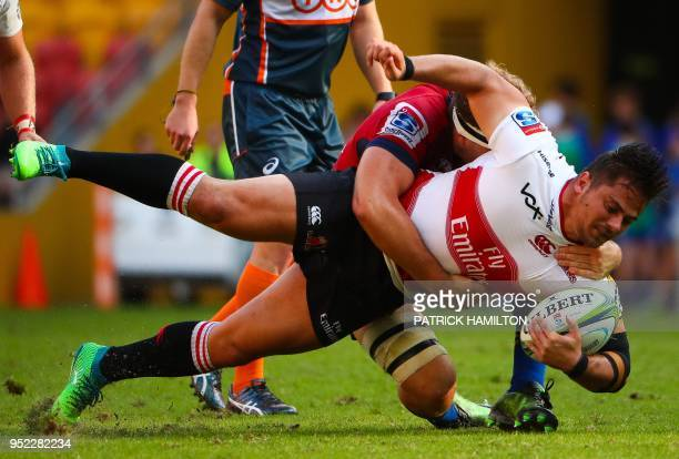 Lions' Rohan Janse van Rensbur is tackled by Red's Angus ScottYoung during the Super Rugby match between Australia's Queensland Reds and South...