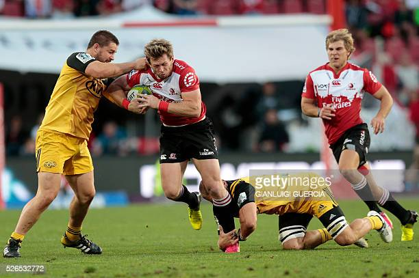Lions South African fullback Ruan Combrinck is tackled by Hurricanes' New Zealand loose forward Brad Shields and New Zealand hooker Dane Coles during...