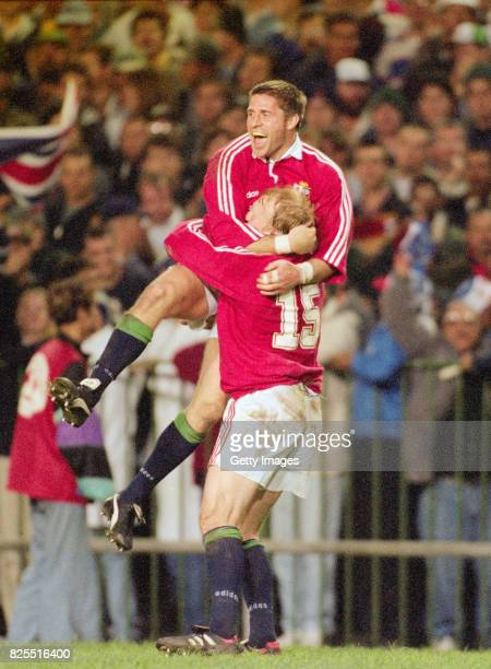 Lions Try scorer Alan Tait is congratulated by Neil Jenkins after scoring his try during the First Test Match between South Africa and British and...