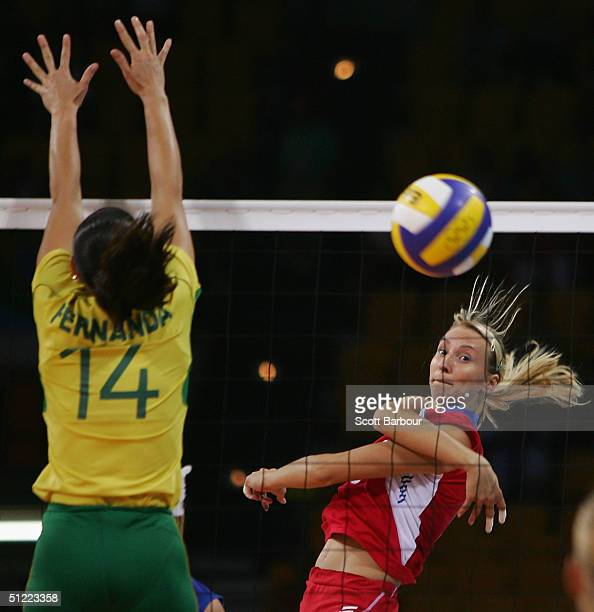 Lioubov Shashkova hits the ball past Fernanda Venturini of Brazil during the Brazil v Russia women's indoor Volleyball semifinal match on August 26...