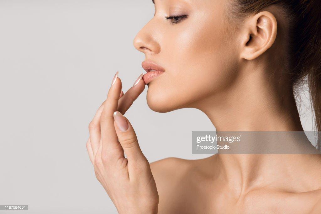Lip augmentation. Beautiful girl touching her lips : Stock Photo