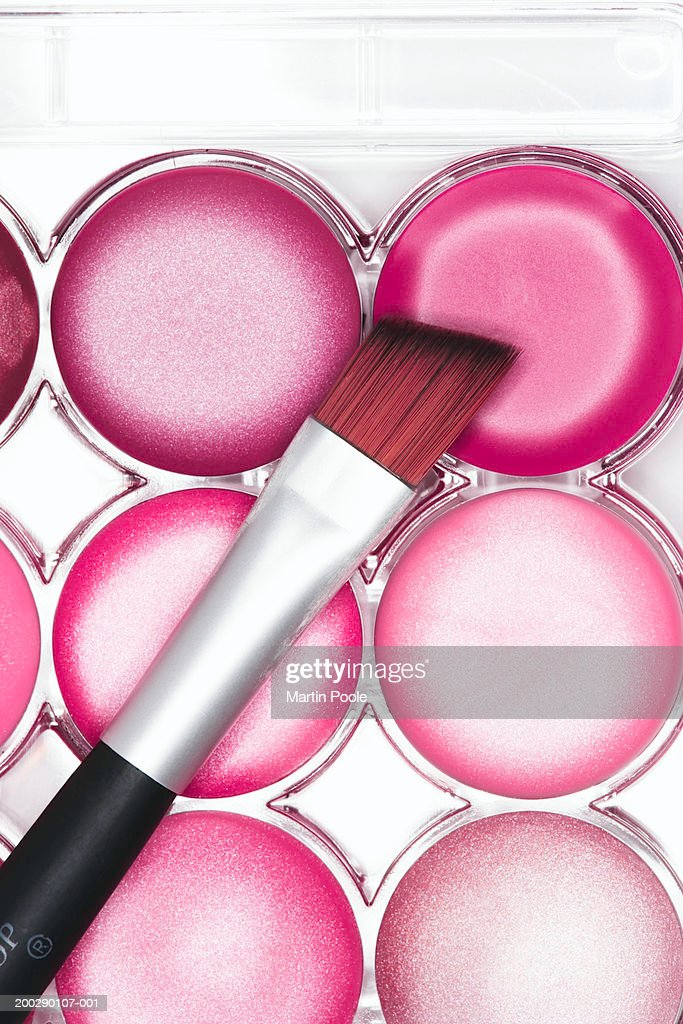 Lip brush resting on pink lip gloss palette, close-up, elevated view : Stock Photo