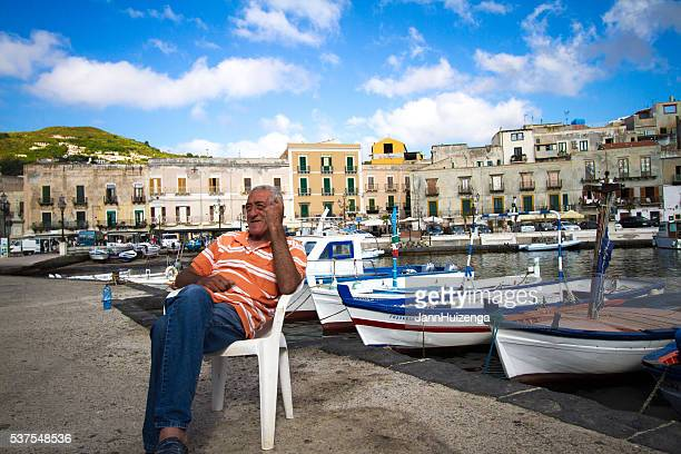 Lipari, Sicily: Fisherman Relaxes Near Small Boats in Marina Corta