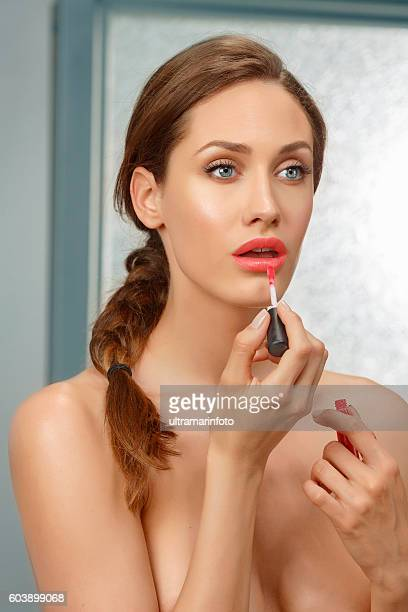 Lips gloss   Beautiful  young women applying red lipstick   Bathroom  Beauty