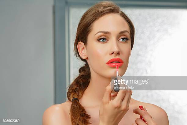 Lips gloss   Beautiful  young women applying red lipstick   Bathroom  Beauty